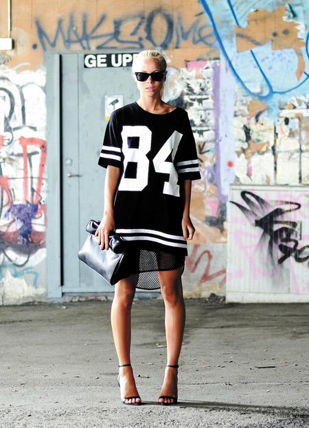 Девушка в черных босоножках на шпильке и черном, спортивном платье с номером