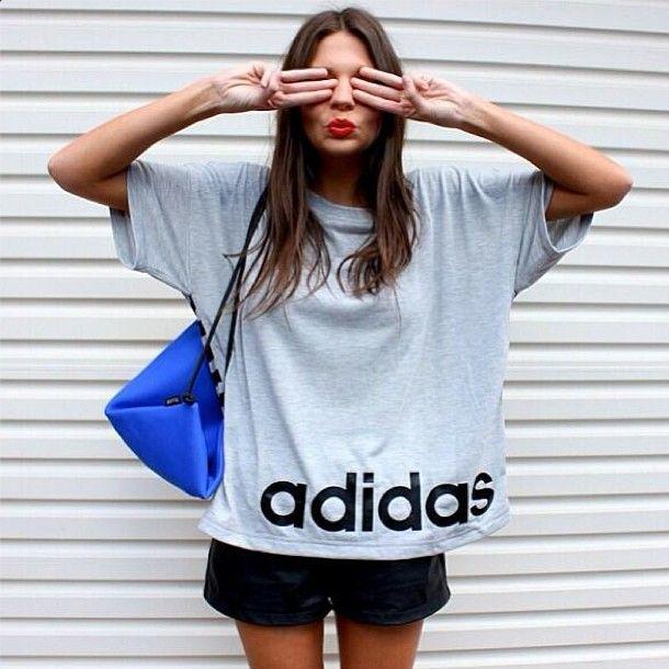 Девушка в коротких, кожаных шортиках и широкой, серой футболке
