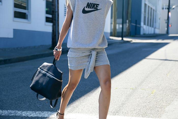 Девушка в короткой, спортивной юбке и серой безрукавке