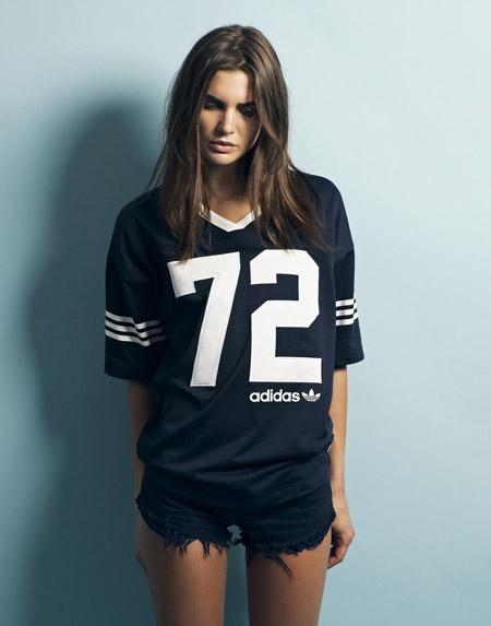 Девушка в кортких, джинсовых шортиках и спортивной футболке adidas