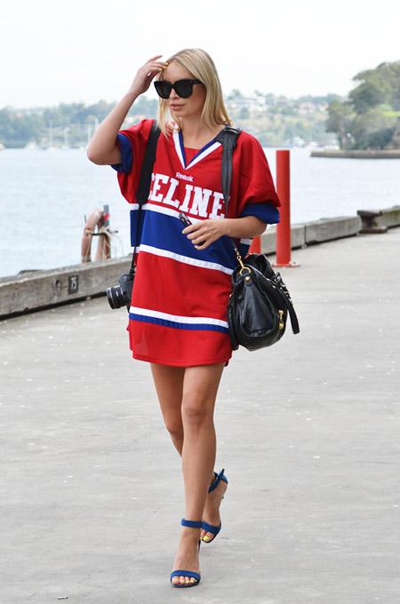 Девушка в красно-синем, платье спортивного стиля и синих босоножках на каблуках