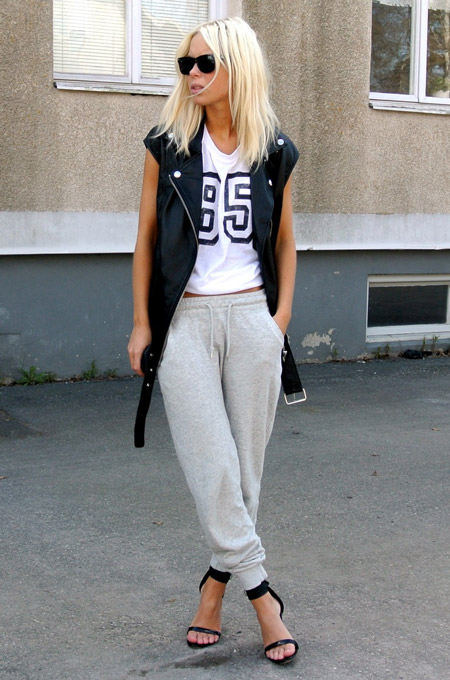 Девушка в серых, спортивных штанах, белой футболке и босоножках на шпильке