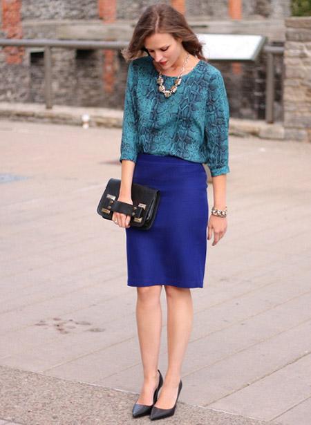 Девушка в синей юбке и блузке со змеиным принтом