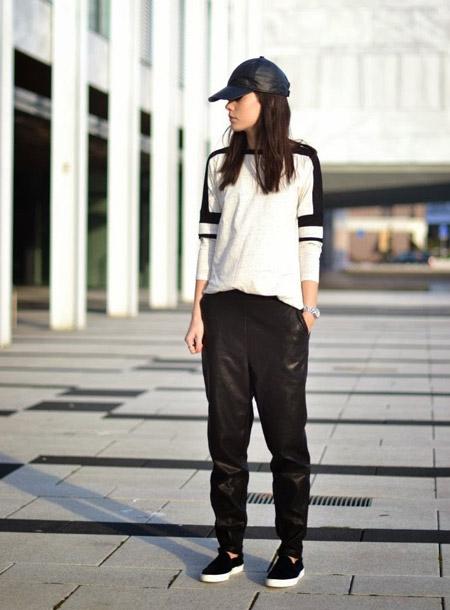 Девушка в спортивных, кожаных штанах, кедах и белой футболке