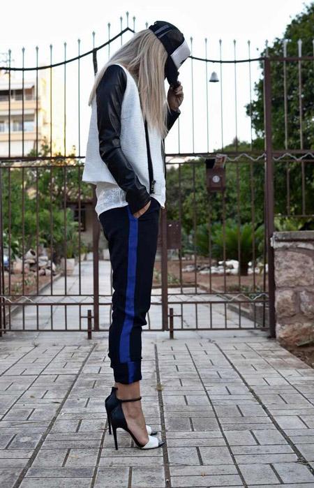 Девушка в спортивных штанах, куртке и туфлях на высоченной шпильке