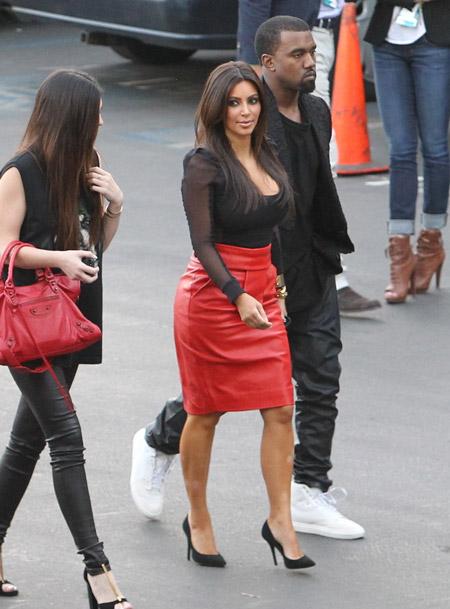 Ким Кардашьян в красной юбке и черной блузке