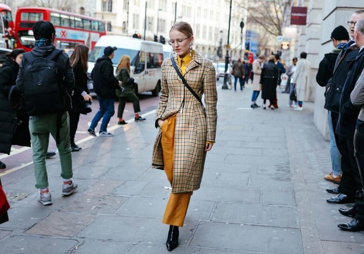 Alexandra Carl в желтых брюках, рубашке и пальто в клетку