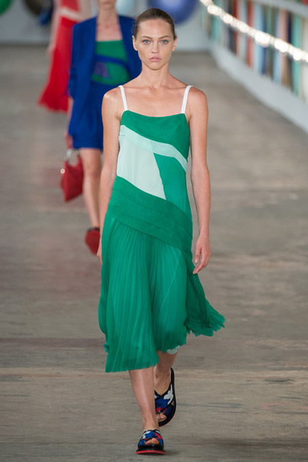 Модель в зеленом платье с плиссированной юбкой от boss hugo boss