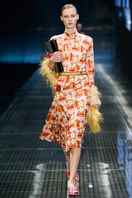 Модель в оранжевом платье миди от prada