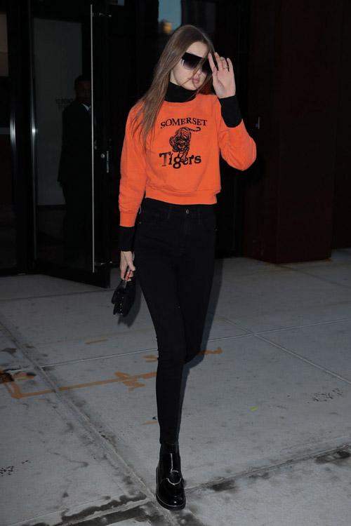 Джиджи Хадид в черных джинсах, водолазке и оранжевой толстовке