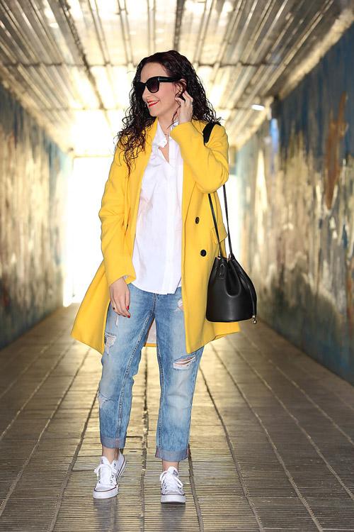 Девушка в джинсах бойфрендах и желтом пальто