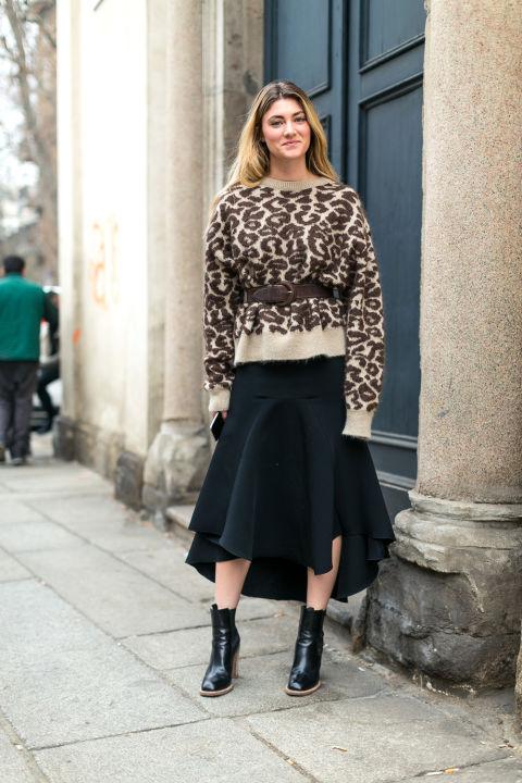 Девушка в черной юбке миди и коричневый свитер