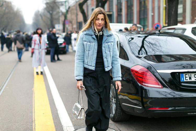 Девушка в черных штанах и голубая куртка
