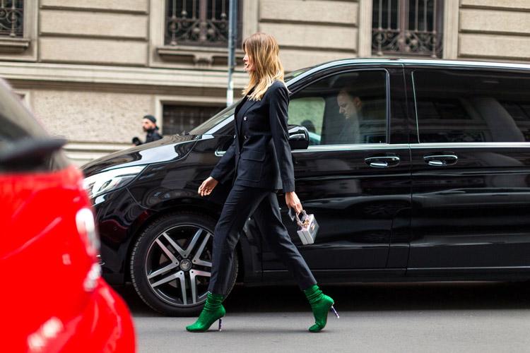 Девушка в черном брючном костюме и зеленые ботильоны