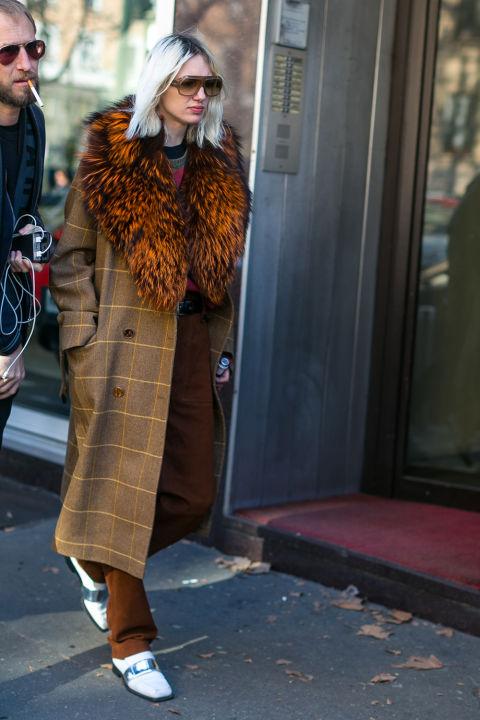 Модель в коричневых брюках и пальто с меховым воротником