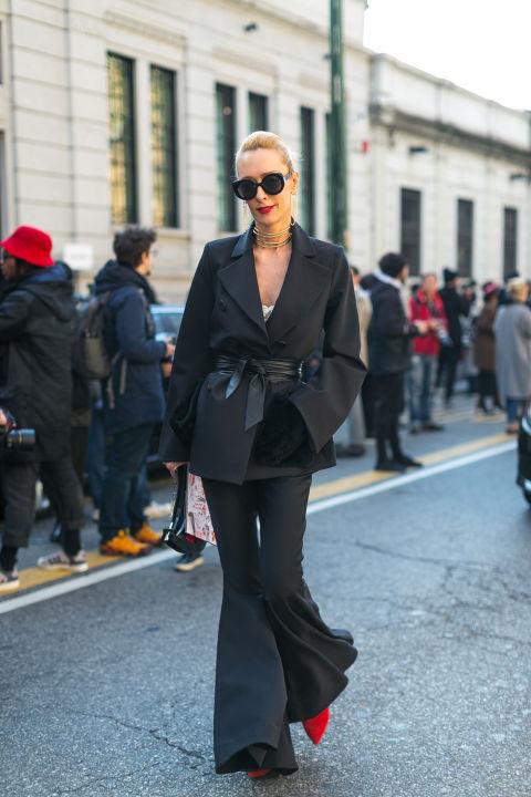 Девушка в черном костюме с брюками клеш, красные туфли