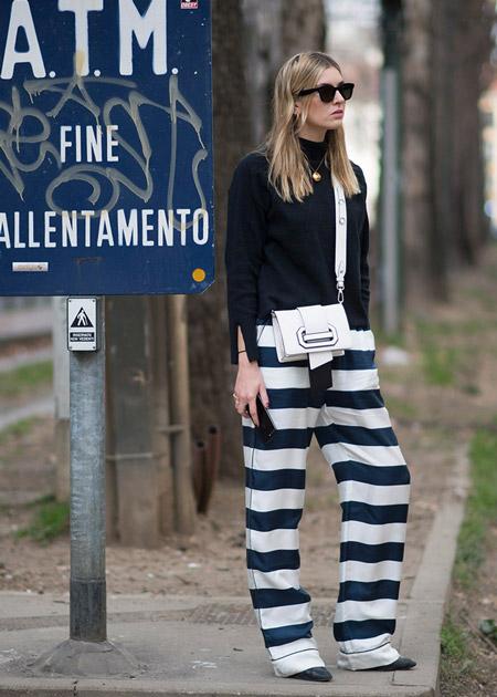 Девушка в бело-синих брюках и черной водолазке