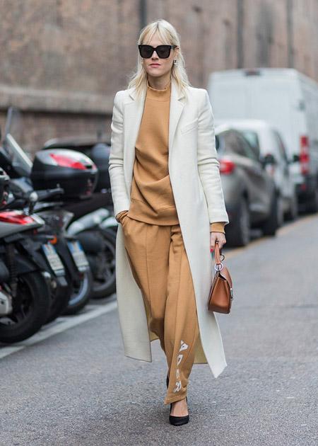 Девушка в бежевом костюме и светлом пальто