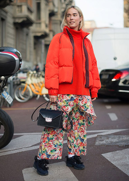 Девушка в цветочных брюках и оранжевом пуховике