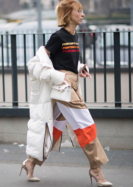 Девушка в широких брюках, черная футболка с надписью и белая куртка