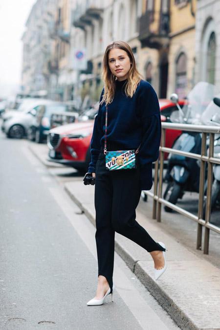 Модель в черных брюках и свитере, сумочка