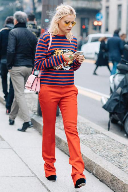 Девушка в красных брюках и свитшоте в полоску