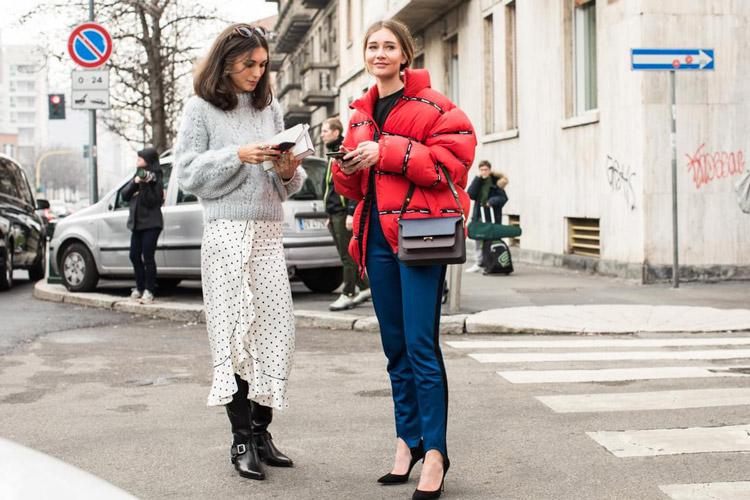 Девушка в белой юбке в черный горох, серый свитер. Девушка в штанах и красном пуховике