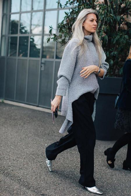 Девушка в черных брюках и удлиненном свитере