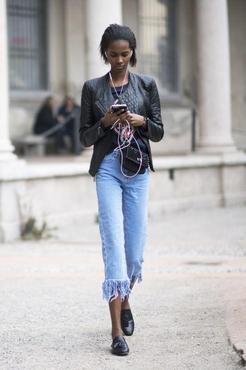 Черную куртку можно дополнить укороченными джинсами с бахромой