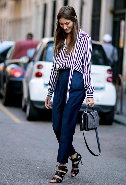 Модель в синих брюках и блузке в полоску