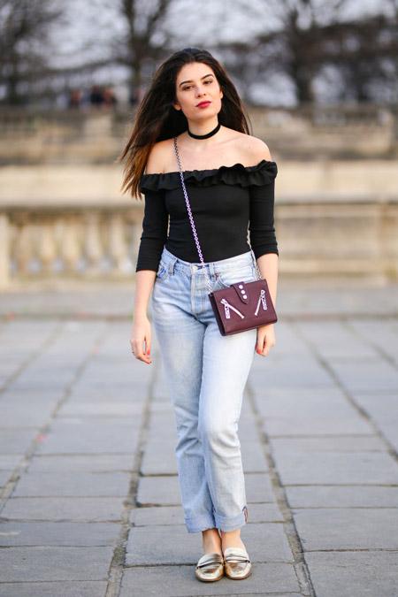 Девушка в джинсах с завышенной талией и черный топ