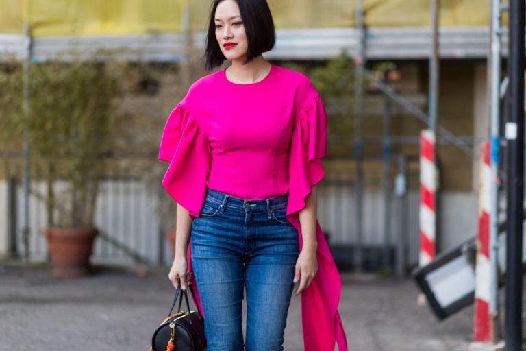 Девушка в джинсах и блузке цвета фуксии