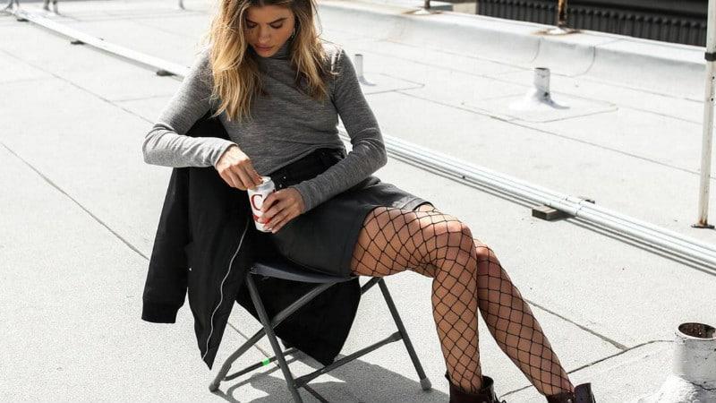 Девушка в черной юбке, серой водолазке и колготках в сетку