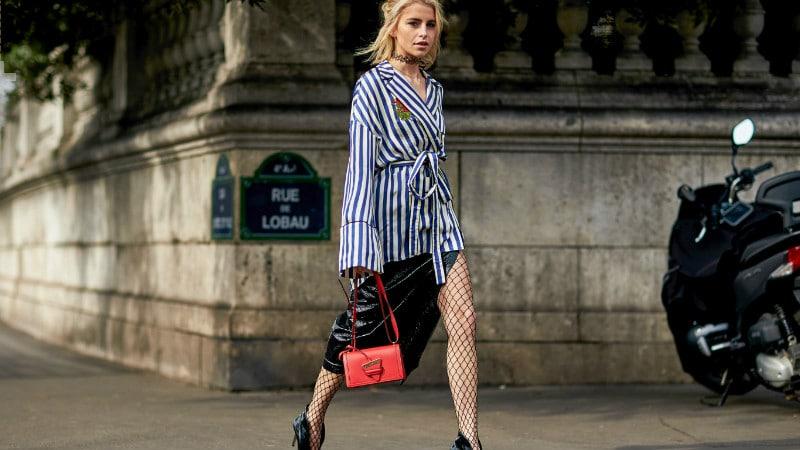 Девушка в черной юбке, пиджак в полоску и колготки в сетку