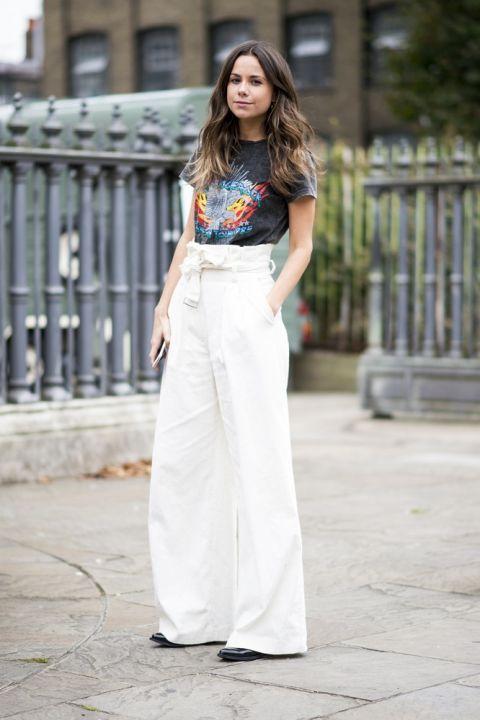 Девушка в белых брюках палаццо и черной футболке с принтом