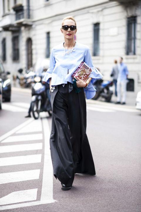 Девушка в черных брюках палаццо и голубой блузке