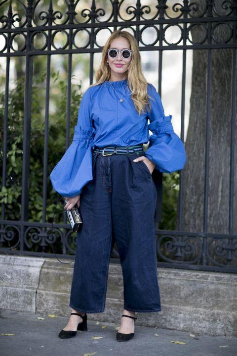 Девушка в джинсовых брюках палаццо и синей блузке