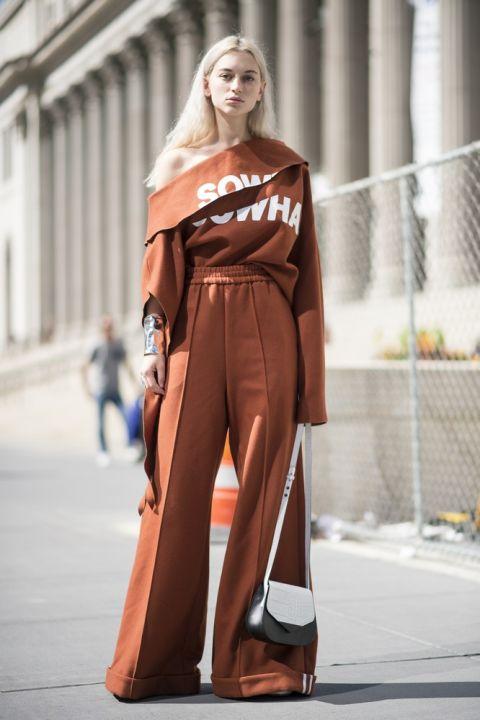 Девушка в оранжевых брюках палаццо на резинке и соответствующий свитшот