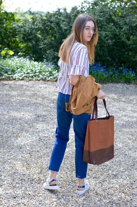 Девушка в полосатой блузке и джинсах герлфрендах