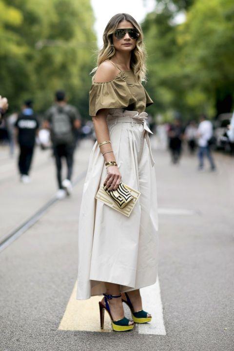 Девушка в укороченных брюках палаццо и кроп-топе с открытыми плечами