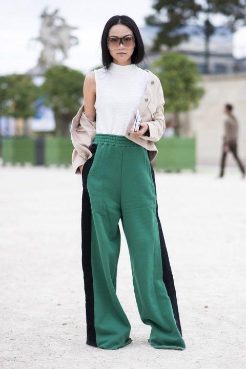 Девушка в зеленых брюках палаццо с черными лампасами и белом топе