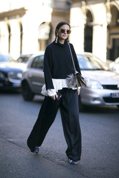 Девушка в черных брюках плаццо и черный свитер