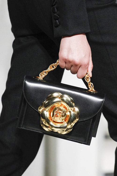 Девушка с черной сумочкой с массивным золотым цветком от oscar de la renta сезон осень 2017 - зима 2018
