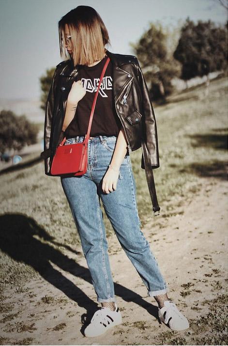Модель в джинсах американках и куртка косуха и красная сумочка
