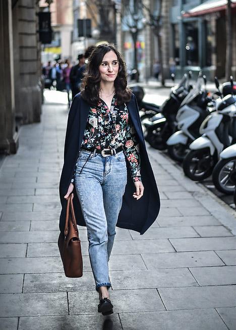Девушка в мом джинсах с ремнем, блузка с принтом и плащ