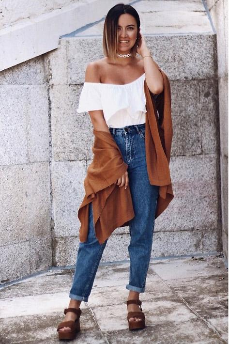 Девушка в мом джинсах и белом топе с открытыми плечами