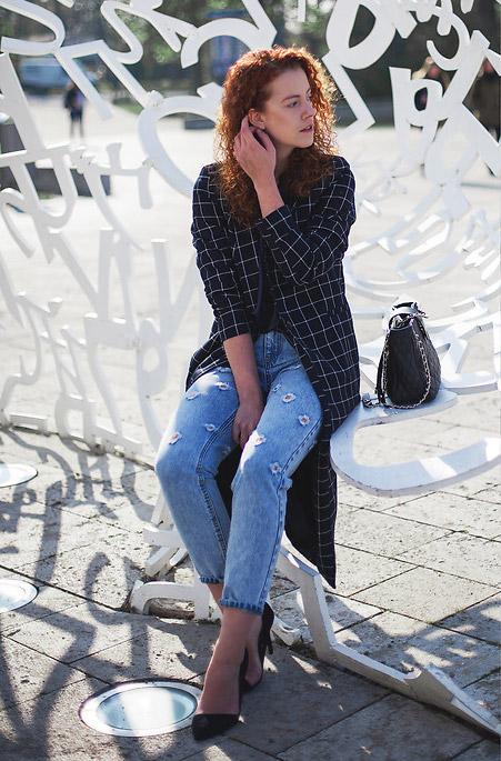 Девушка в мом джинсах и черный плащ в клетку