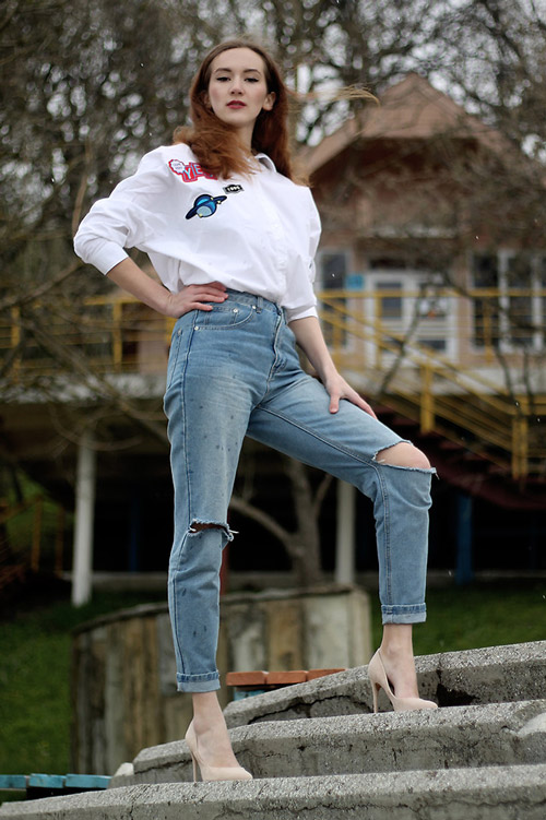 Девушка в рваных джинсах и белой рубашке