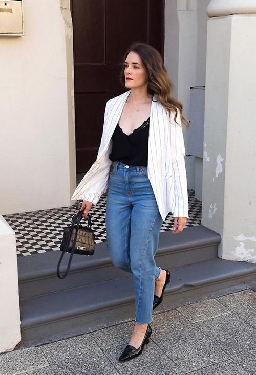 Девушка в джинсах американках, черный топ и пиджак