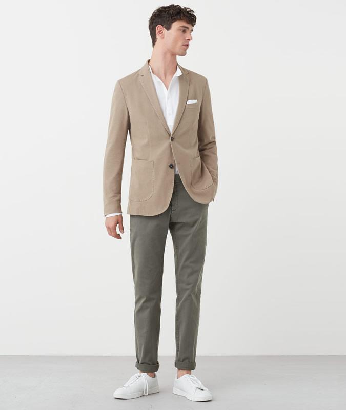 Парень в бежевом пиджаке и светло-серых брюках